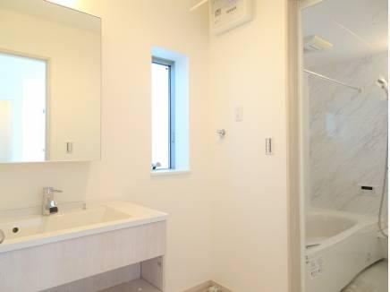 清潔感溢れるパウダールーム、大理石風のクロスを使用したバスルーム