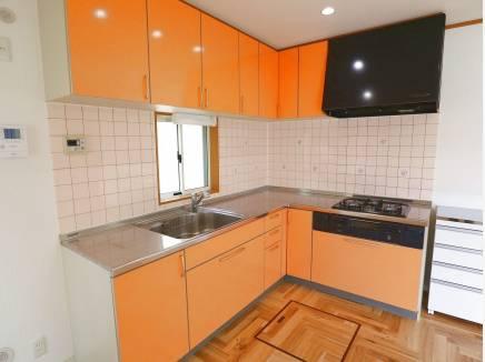 オレンジ色がアクセントのL型キッチン。