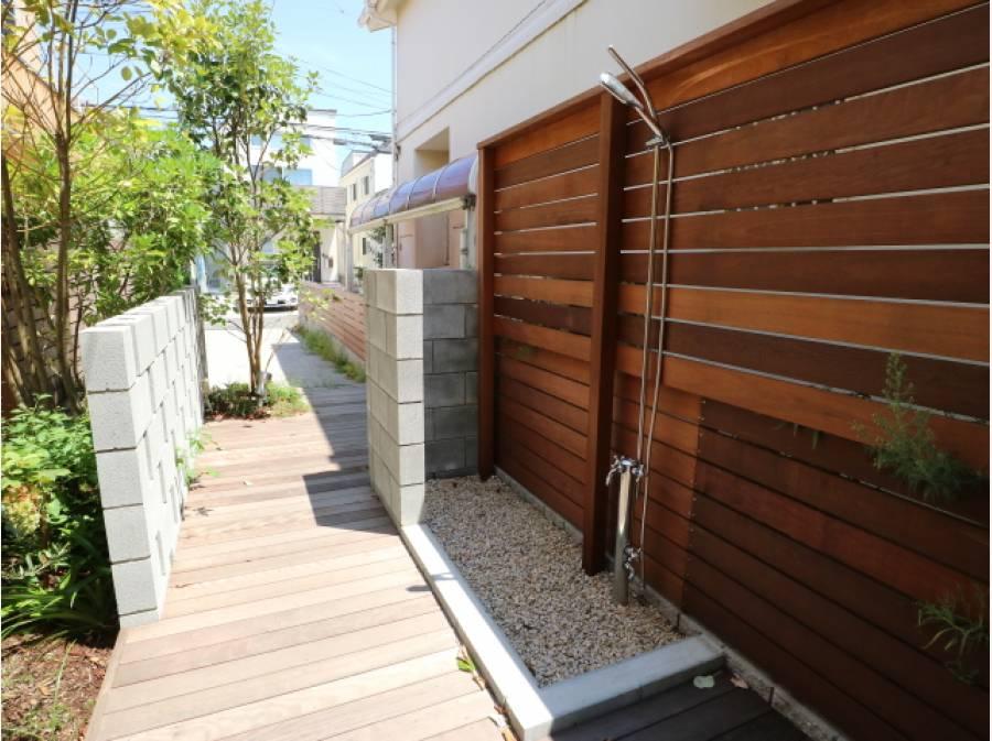 玄関までは楽しげなウッドデッキのアプローチ。外シャワーも配置