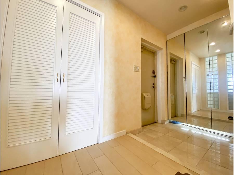 玄関は大理石調のタイル張り、収納は全体が鏡張りです