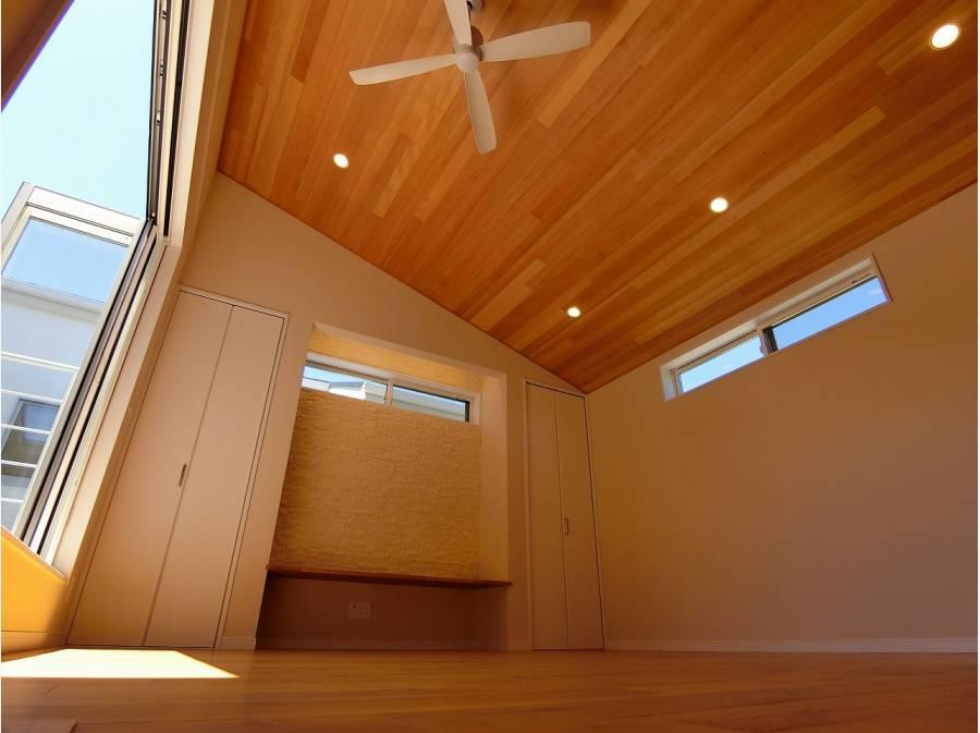 勾配天井にシーリングファンがある開放的なリビング約11帖。