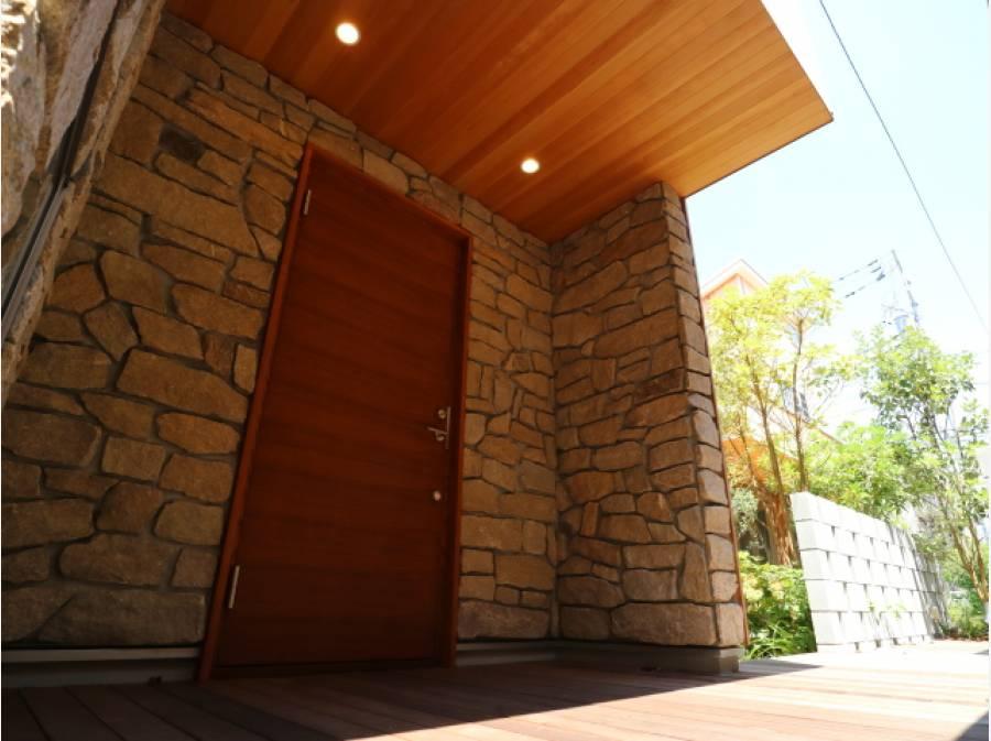 迫力のあるストーン仕上げの玄関に重厚な木製ドアが映えます